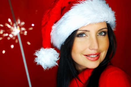 Portrait of beautiful brunette woman wearing santa claus hat on red background photo