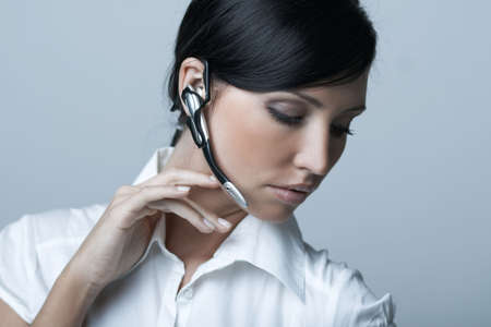 businesswear: Beautiful brunette business woman with wireless headset isolated on clear background