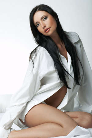 Beautiful brunette woman on bed, wearing white large casual shirt photo