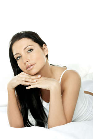 Portrait of Fresh and Beautiful brunette woman on bed photo