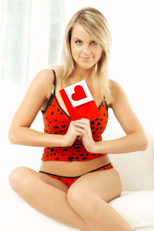 Young beautiful woman with a card in bed wearing red lingerie photo