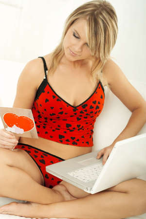 Young beautiful woman with a card in bed wearing red lingerie working on laptop computer photo