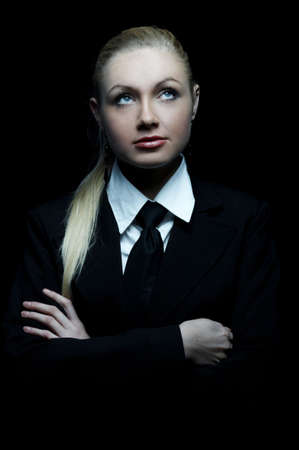 businesswear: Beautiful business woman wearing black tie and jacket isolated on black background