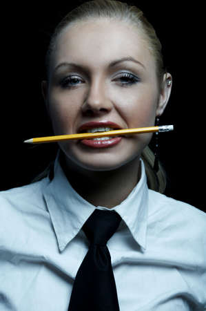 businesswear: Beautiful business woman wearing black tie and white shirt isolated on black background holding pencil in her mouth Stock Photo