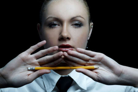 Beautiful business woman wearing black tie and white shirt isolated on black background holding pencil Stock Photo - 739256