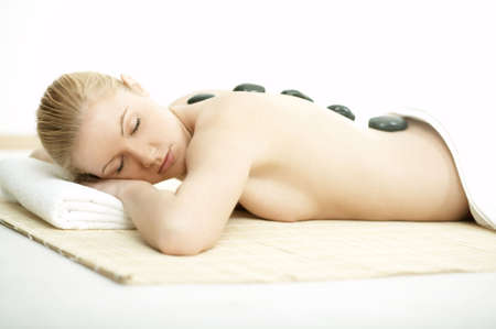 Young blond woman getting lastone treatment at spa photo