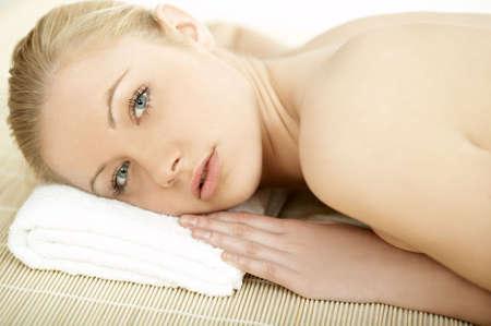 Portrait of Fresh and Beautiful blond woman laying on bamboo mat photo