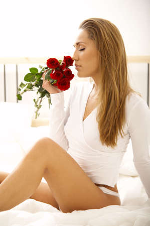 Portrait of Fresh and Beautiful brunette woman on bed with red roses photo
