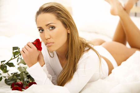 Portrait of Fresh and Beautiful brunette woman on bed with red roses Stock Photo - 749701