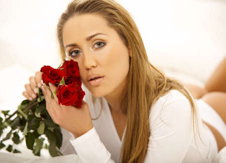 Portrait of Fresh and Beautiful brunette woman on bed with red roses Stock Photo - 749699