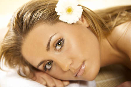 Portrait of Fresh and Beautiful blond woman laying on bamboo mat around flowers and taking spa treatment photo