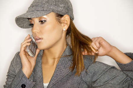 Beautiful business woman wearing jacket and hat on white background and using cell phone photo