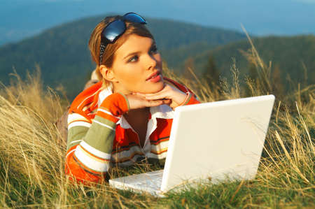 Young business woman relaxing, working on laptop computer on meadow photo