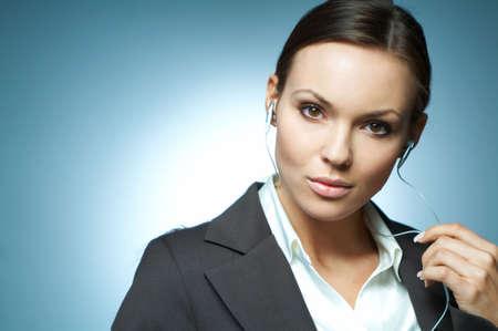 morena sexy: Hermosa y sexy mujer morena de negocios aislados en claro los antecedentes con los auriculares es escuchar la m�sica.