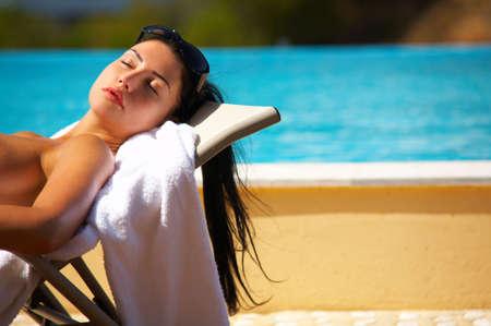 sunbath: Beautiful young Sexy woman in bikini during sunbath next to swimming pool Stock Photo