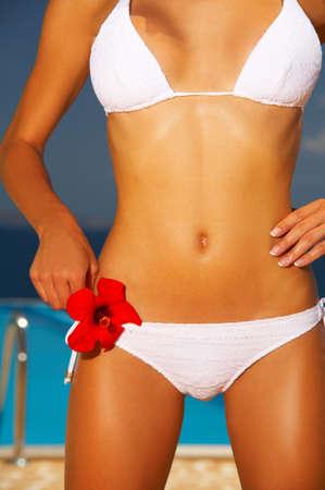 sunbath: Mooie jonge vrouw Sexy lichaam in bikini tijdens zonnebaden naast zwembad
