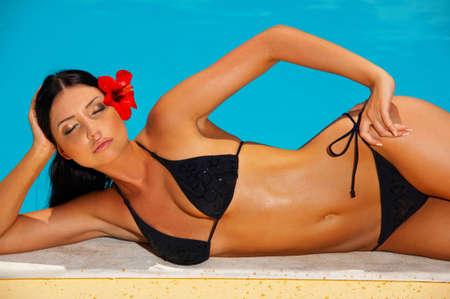 Beautiful young Sexy woman laying in bikini during sunbath next to swimming pool Stock Photo - 950448