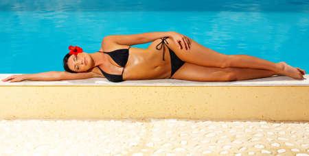 sunbath: Sexy mooie jonge vrouw tot in bikini tijdens zonnebaden naast zwembad