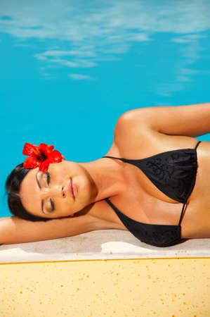 Beautiful young Sexy woman laying in bikini during sunbath next to swimming pool Stock Photo - 953499