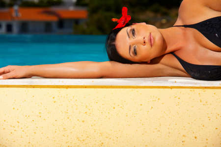 Beautiful young Sexy woman laying in bikini during sunbath next to swimming pool photo