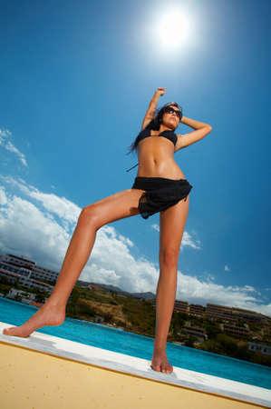 sexy woman standing: Sexy mujer hermosa joven de pie negro en bikini junto a la piscina