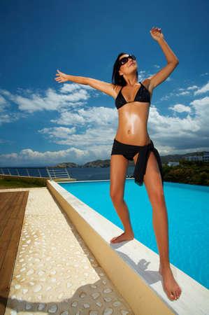 sexy woman standing: Sexy mujer hermosa joven de pie en bikini junto a la piscina  Foto de archivo