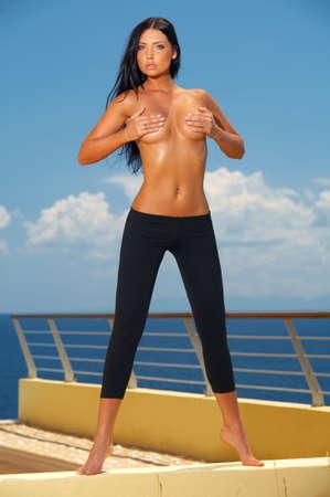 morena sexy: Mujer atractiva joven hermosa del brunette que se presenta en desgaste de la aptitud Foto de archivo