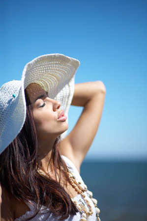 20-25 years old Beautiful Woman on the beach, wearing hat photo
