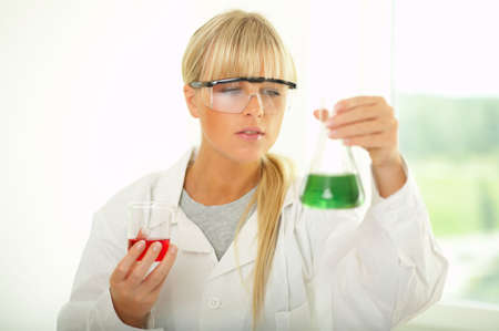 experimenting: Female lab worker testing and experimenting Stock Photo