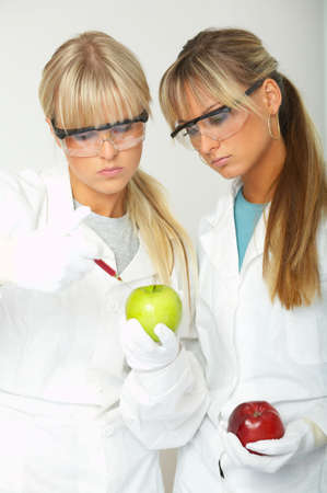 modifying: Female scientists injecting liquid into a apple Stock Photo