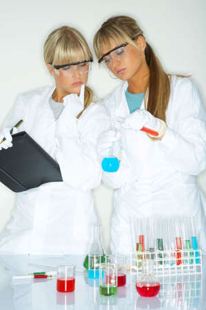 experimenting: Beautiful female lab workers testing and experimenting Stock Photo