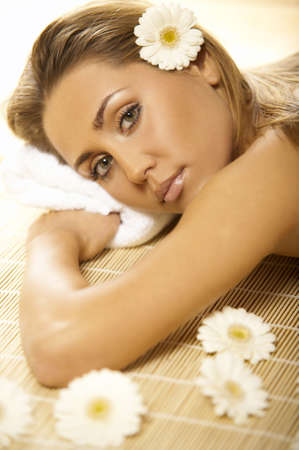 woman laying: Portrait of Fresh and Beautiful blond woman laying on bamboo mat around flowers and taking spa treatment