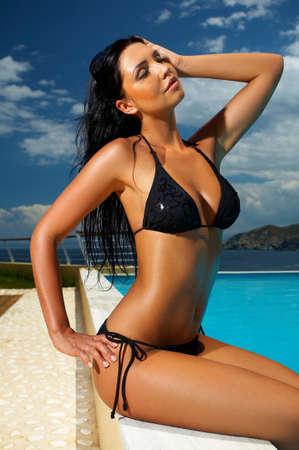 sunbathing: Beautiful young Sexy woman sitting in bikini next to swimming pool