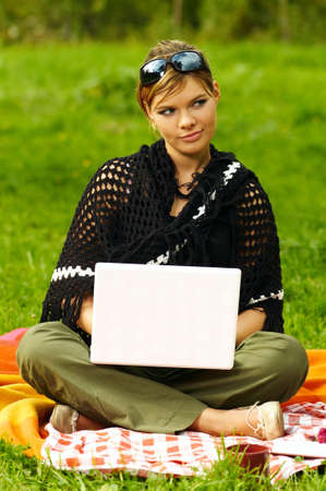 Young business woman working on laptop computer during picnic on green meadows outdoors photo