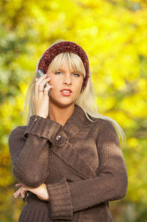 20 25 years old: 20-25 years old beautiful sexy woman portrait using cell phone in natural autumn outdoors Stock Photo