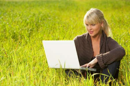 leasure: 20-25 anni bella donna sexy ritratto di lavoro sul computer portatile su erba verde prato  Archivio Fotografico