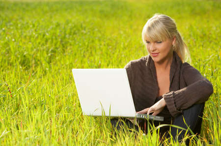 20 25 years old: 20-25 years old beautiful sexy woman portrait working on laptop computer on green grass meadow Stock Photo