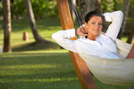 20-25 years woman portrait relaxing on hammock at exotic surrounding, bali indonesia photo