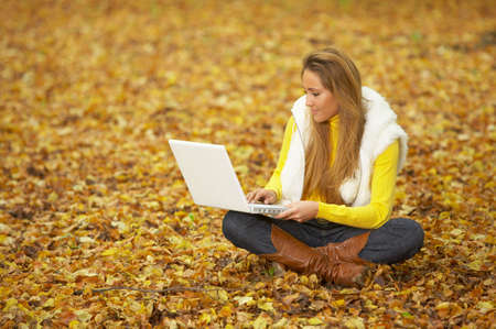 20 25 years old: 20-25 years old beautiful sexy woman portrait working on laptop computer in natural autumn outdoors