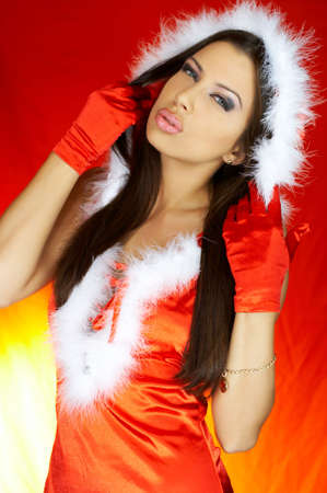 Portrait of beautiful brunette woman wearing sexy santa claus clothes on red background Stock Photo - 2146678