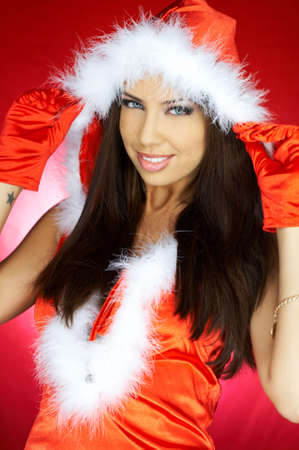 Portrait of beautiful brunette woman wearing sexy santa claus clothes on red background Stock Photo - 2146690