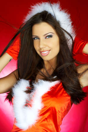 Portrait of beautiful brunette woman wearing sexy santa claus clothes on red background Stock Photo - 2146685
