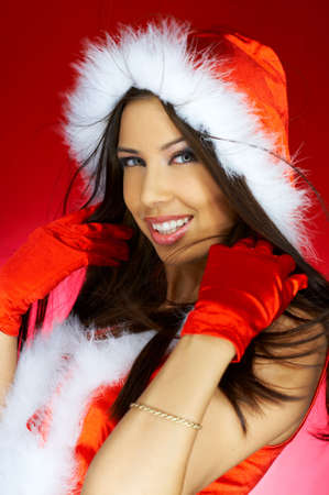 Portrait of beautiful brunette woman wearing sexy santa claus clothes on red background Stock Photo - 2146671