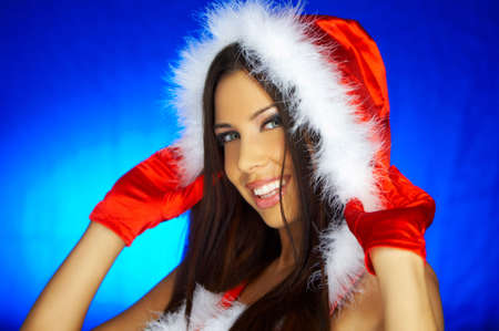 Portrait of beautiful brunette woman wearing sexy santa claus clothes on blue background Stock Photo - 2146663