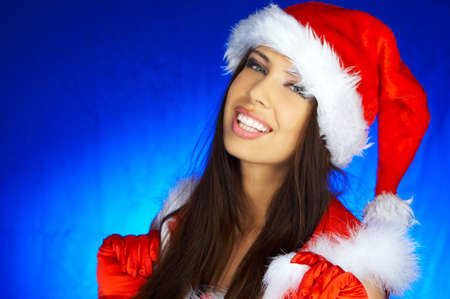 Portrait of beautiful brunette woman wearing sexy santa claus clothes on blue background Stock Photo - 2146662