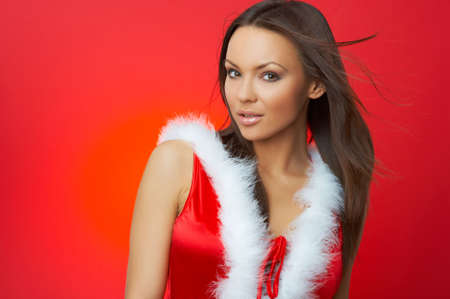 sexy santa: Portrait of beautiful brunette woman wearing sexy santa claus clothes on red background Stock Photo