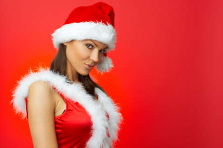 sexy young girls: Portrait of beautiful brunette woman wearing sexy santa claus clothes on red background Фото со стока
