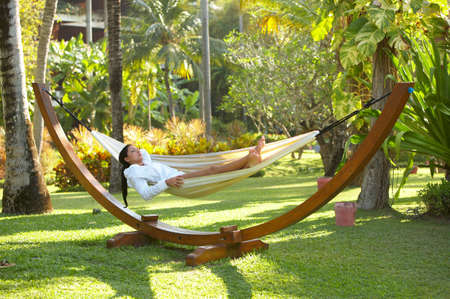 surrounding: Woman relaxing on hammock at exotic surrounding at bali indonesia Stock Photo