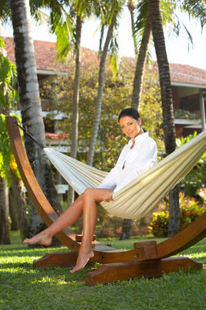 Woman relaxing on hammock at exotic surrounding at bali indonesia photo