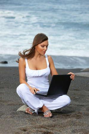 Woman on the black Fuerteventuras beach using laptop  photo
